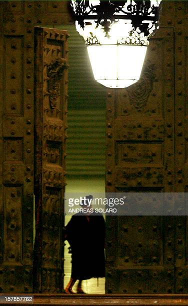 A Swiss guard closes the bronze doors of the Vatican at 8pm at St Peter's Square in the Vatican City 02 April 2005 an hour and a half before the...