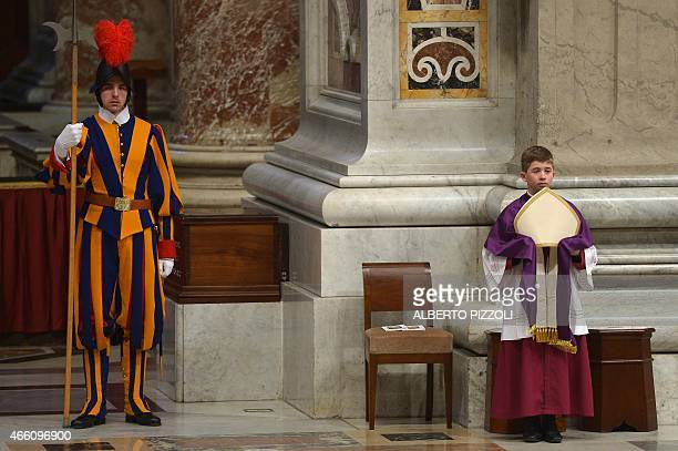 A Swiss guard stands near an altar boy holding the papal mitre during a penitential ceremony led by Pope Francis on March 13 2015 at St Peter's...