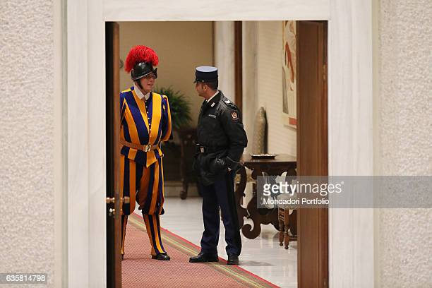 A Swiss Guard the old army protecting the Pope standing beside a security guard behind the door of the Paul VI Audience Hall just opened Pope Francis...