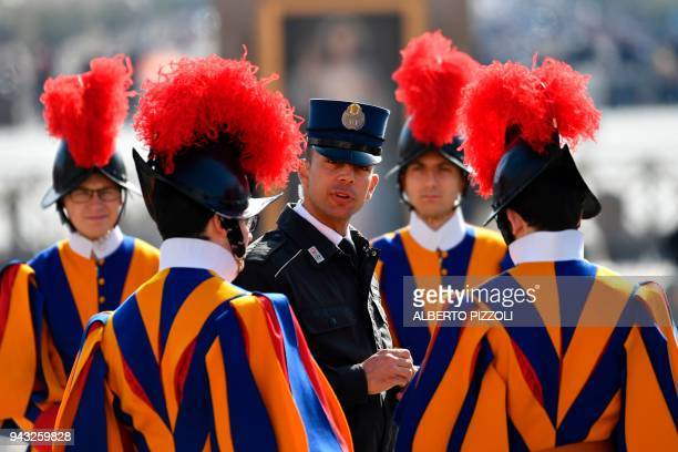 Swiss Guards speak with a Vatican's gendarme before a Holy mass on April 8, 2018 in Vatican. / AFP PHOTO / Alberto PIZZOLI