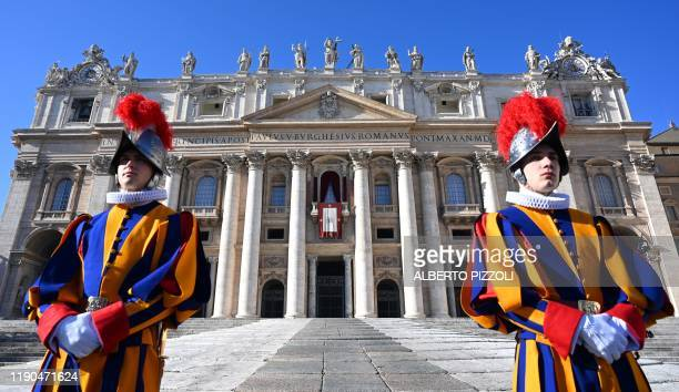 Swiss guards stand in front of St Peter's Basilica before the appearance of Pope Francis at the balcony for the traditional Urbi et Orbi Christmas...