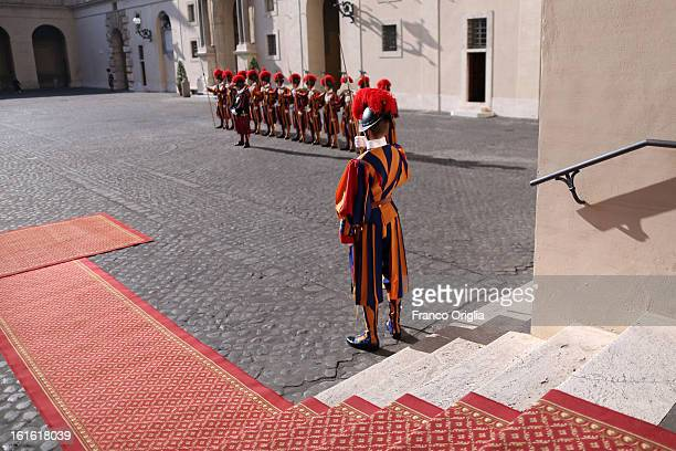 Swiss guards stand on attention at the Cortile di San Damaso of the Apostolic Palace on October 25 2012 in Vatican City Vatican Pope Sixtus V built...