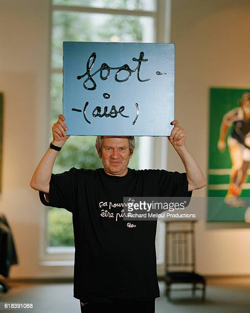 Swiss installation artist Ben Vautier holds up a hand painted sign that reads foot at a Paris art exhibit on the theme of soccer The sign is a pun on...