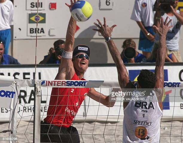 Swiss Martin Laciga spikes as Brazilian Jose Loiola tries to block his action during the finals of the beachvolleyball championsdhips held in...