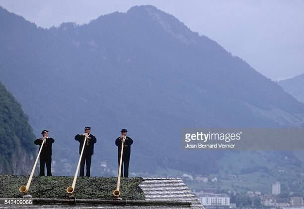 Swiss men play alpenhorns from a rooftop near Rutli Switzerland in celebration of the Swiss Confederation's 700th anniversary Rutli is a meadow in...