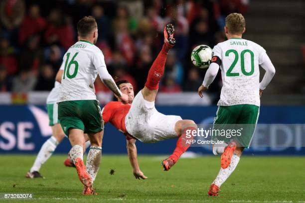 Swiss midfielder Blerim Dzemaili vies for the ball with Northern Ireland's midfielders Oliver Norwood and George Saville during the FIFA 2018 World...