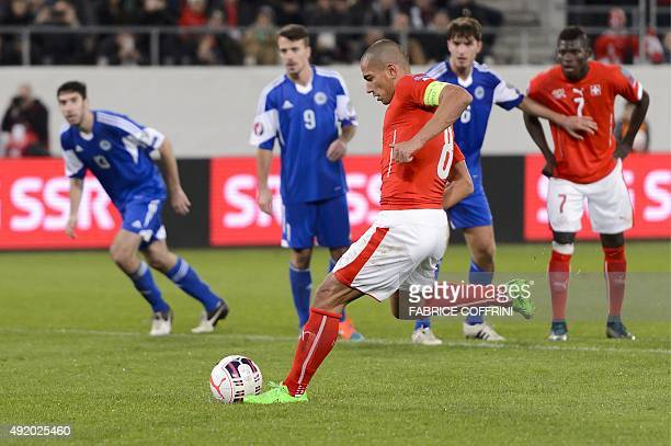 Swiss midfielder Gokhan Inler aims to score a penalty during the Euro 2016 Group E qualifying football match between Switzerland and San Marino on...