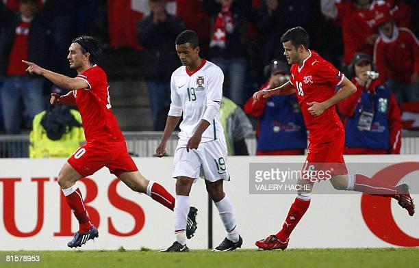 Swiss midfielder Hakan Yakin and Swiss forward Tranquillo Barnetta celebrate after scoring a penalty as Portuguese defender Miguel looks dejected...