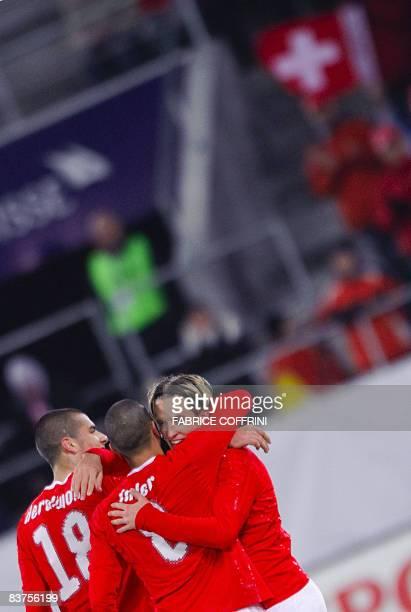 Swiss midfielder Reto Ziegler reacts with teammate midfielder Goekhan Inler and forward Eren Derdiyok after he scored during a friendly football...