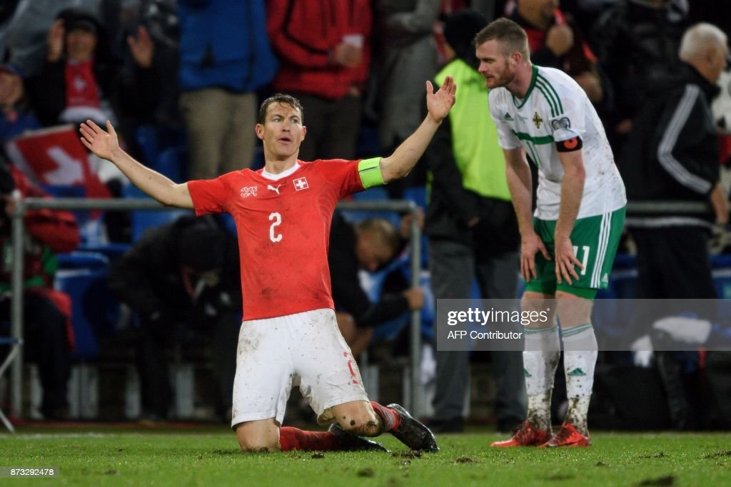 Swiss midfielder Stephan Lichtsteiner (L) celebrates his team's qualification next to Northern Ireland's midfielder Chris Brunt at the end of the FIFA 2018 World Cup play-off second leg football match between Switzerland and Northern Ireland at St. at St. Jakob-Park Stadium on November 12, 2017. / AFP PHOTO / Fabrice COFFRINI