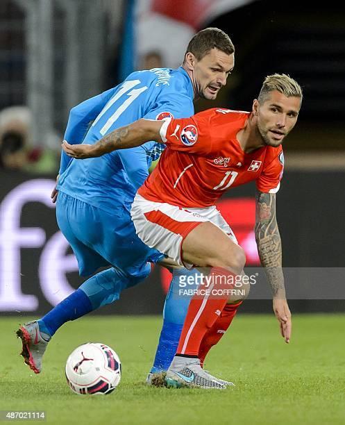 Swiss midfielder Valon Behrami vies with Slovenian forward Milivoje Novakovic during the Euro 2016 qualifying football match between Switzerland and...