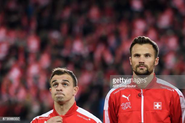 Swiss midfielder Xherdan Shaqiri and teammate foward Haris Seferovic look on during the national anthem prior to the FIFA 2018 World Cup playoff...