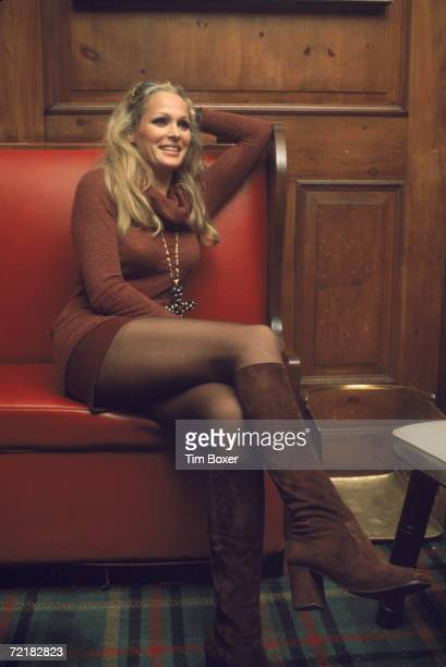 Swiss motion picture actress Ursual Andress sits on a red leather couch in a miniskirt high boots and turtleneck sweater with her legs crossed 1970s