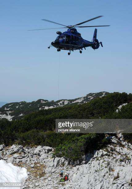 Swiss mountain rescues specialist arrive in a helicopter near the entrance to Riesending cave at Untersberg mountain near Marktschellenberg Germany...