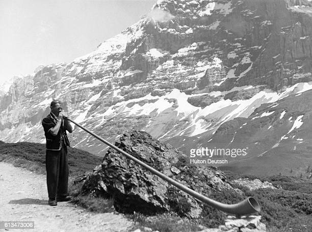 A Swiss mountaineer blows an alpenhorn with the Alps in the background