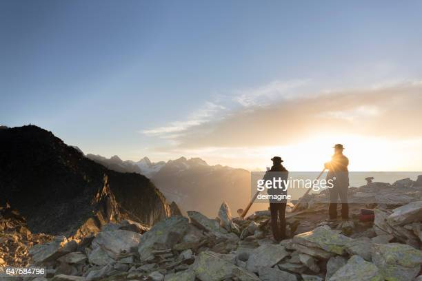 Swiss musicians playing  traditional horn on top of Mount Eggishorn during sunrise.