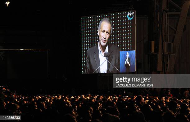 Swiss Muslim intellectual and professor Tariq Ramadan appears on a giant screen as he speaks during a meeting focused on 'Faith and Resistance Reform...