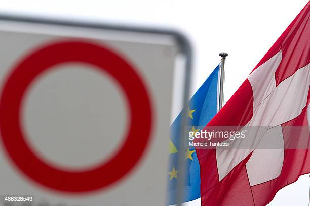 A swiss National Flag and an european Flag wave beside a road sign at the tree nations frontier on February 10 2014 at BaselSwitzerland Swiss...