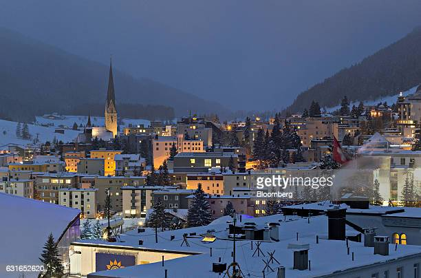 A Swiss national flag flies above a snow covered rooftop as the spire of St Johann church left stands above buildings illuminated at dusk in Davos...