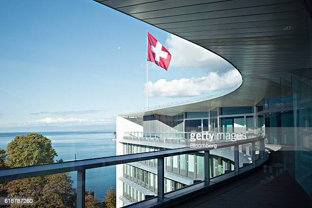 A Swiss national flag flies above the headquarters of the Nestle SA headquarters as Lac Leman is seen beyond in Vevey Switzerland on Thursday Oct 20...