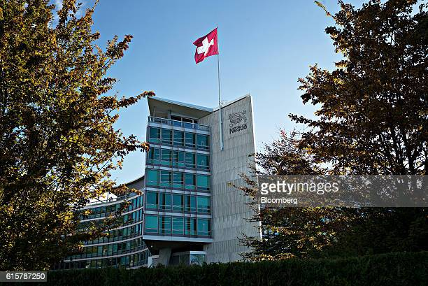 A Swiss national flag flies above the headquarters of the Nestle SA headquarters in Vevey Switzerland on Thursday Oct 20 2016 Nestle cut its fullyear...