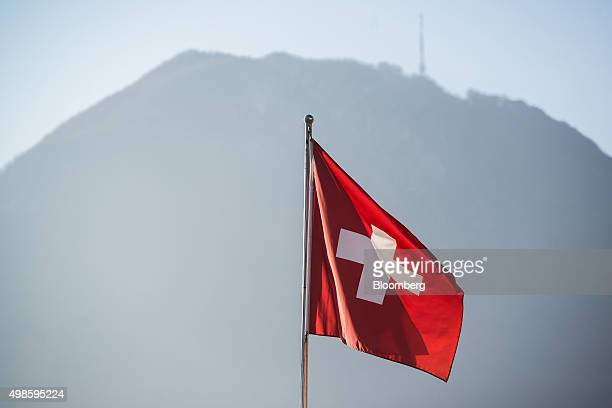 A Swiss national flag flies as Monte San Salvatore stands in the background in Lugano Switzerland on Friday Nov 20 2015 The franc is still too strong...