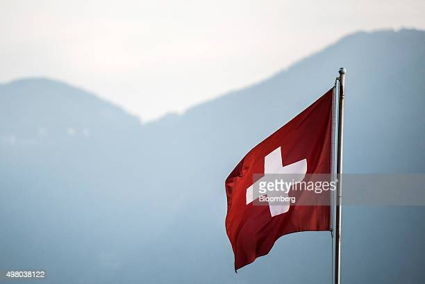 A Swiss national flag flies in Lugano Switzerland on Thursday Nov 19 2015 The franc is still too strong and the economy not yet back to full health...