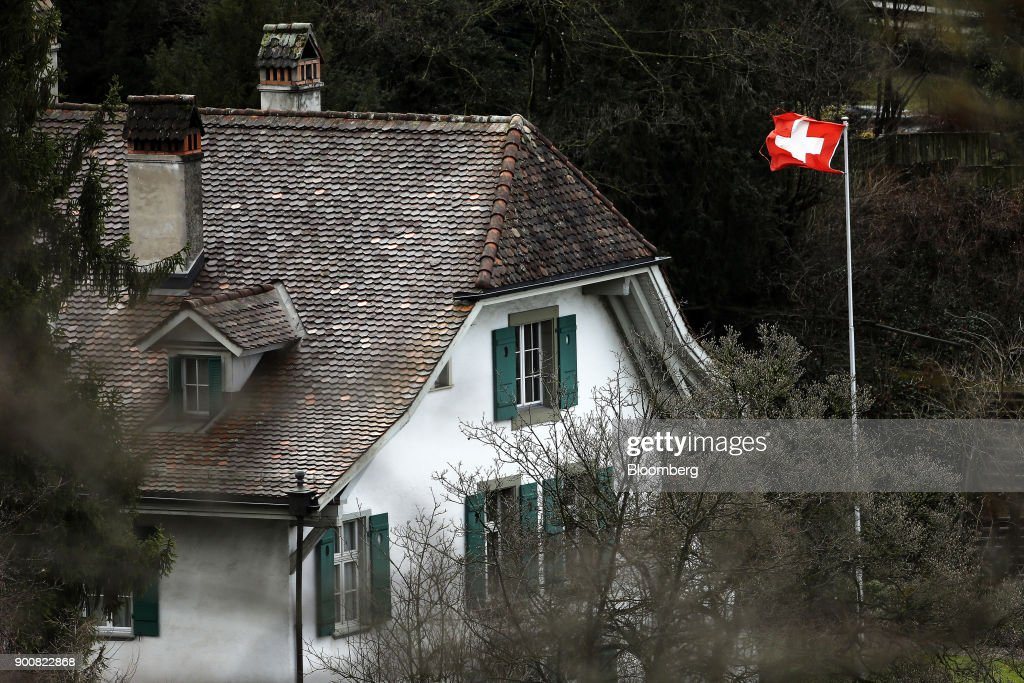A Swiss national flag flies outside a traditional residential property in Bern, Switzerland, on Monday, Jan. 1, 2018. The supply of uninhabited apartments for rent has increased faster than the Swiss population has grown. Photographer: Stefan Wermuth/Bloomberg via Getty Images