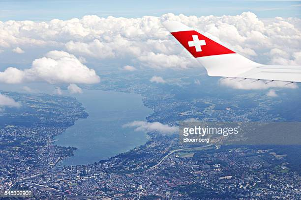 A Swiss national flag sits on the wingtip of a Bombardier Inc CS 100 C Series jet operated by Swiss International Air Lines AG as Lake Zurich sits...