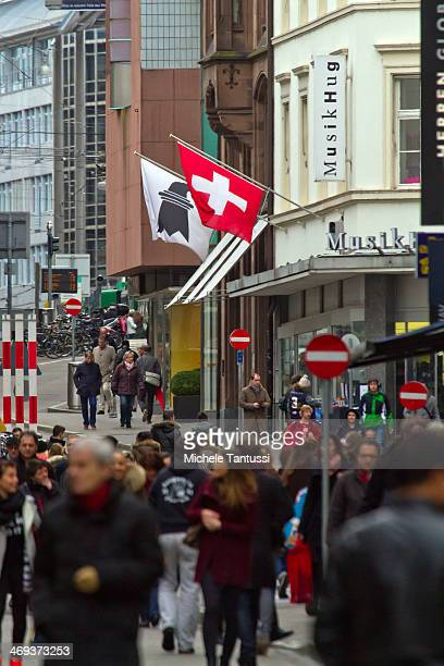 Swiss National Flag waves as pedestrians walk in the Freie strasse on February 14 2014 at BaselSwitzerland Swiss citizens voted with a narrow...