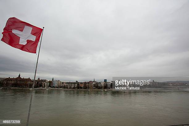 Swiss National Flag waves at the rhine River on February 14 2014 at BaselSwitzerland Swiss citizens voted with a narrow majority in favour of...