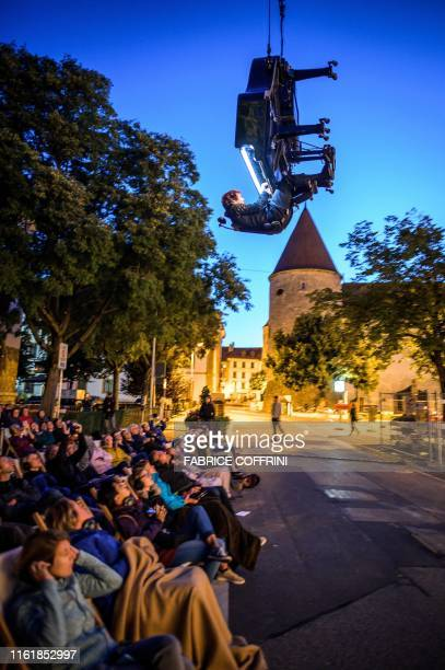 Swiss pianist and composer Alain Roche performs Chantier suspended in the air with his grand piano under a moving crane at dawn on August 16 2019...