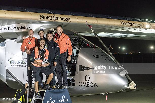 Swiss pilot Bertrand Piccard and alternate pilot Andre Boschberg also of Switzerland react with crew members infront of Solar Impulse 2 the...