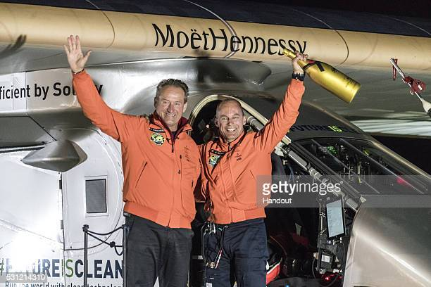 Swiss pilot Bertrand Piccard and alternate pilot Andre Boschberg also of Switzerland react infront of Solar Impulse 2 the solarpwered plane which...