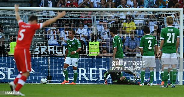 A Swiss player cheers as Germany national team players react in disappointement at the end of the International friendly football match between...