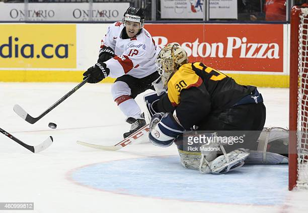 TORONTO JANUARY 3 Swiss player Jason Fuchs tries to beat German goalie Kevin Reich 2015 IIHF World Junior Championship hockey between Germany and...