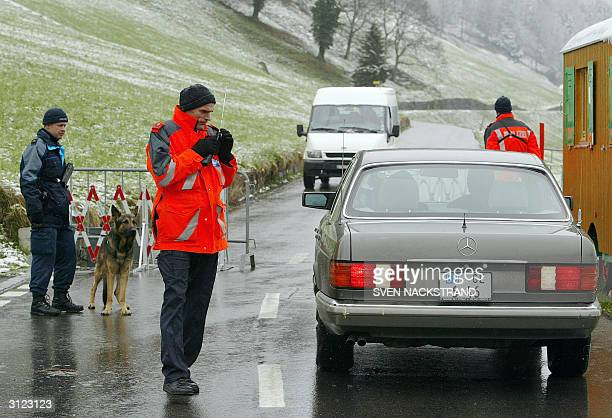 Swiss police check a Greek diplomatic car at a checkpoint leading to the sealed of hotel in Burgenstock near Lucerne 23 March 2004 where Greece and...