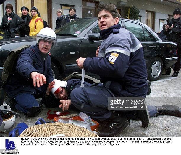 Swiss police officer is tended to after he was hurt by a protester during a demonstration outside of the World Economic Forum in Davos Switzerland...