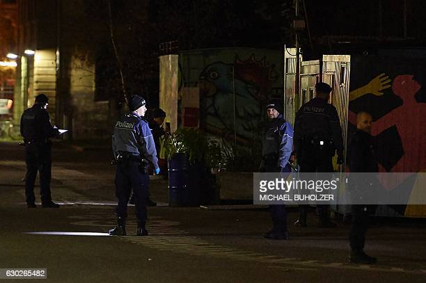 Swiss police officers are seen searching the area near a Muslim prayer hall central Zurich on December 19 after three people were injured by gunfire...