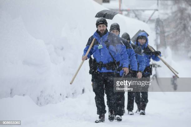Swiss police officers carry shovels to clear snow from the street after heavy snowfall ahead of the World Economic Forum in Davos Switzerland on...