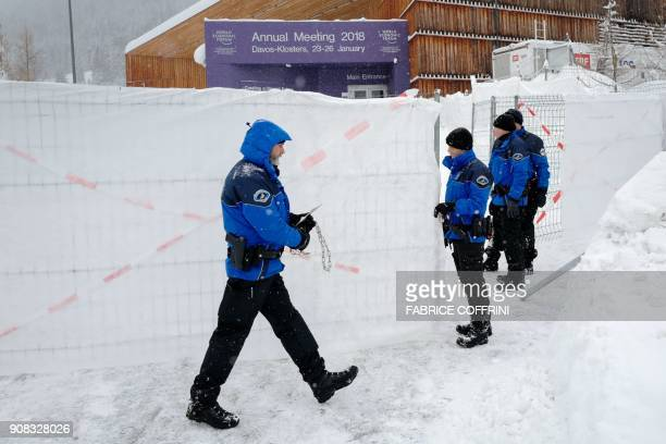 Swiss police officers check the fencing and grounds outside the Davos Congress Centre ahead of the opening of the annual World Economic Forum 2018...