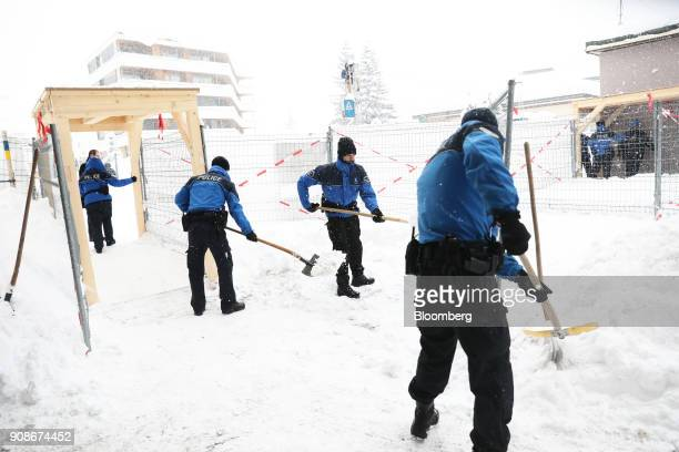 Swiss police officers clear the snow beside security fences outside the Congress Center during heavy snowfall ahead of the World Economic Forum in...