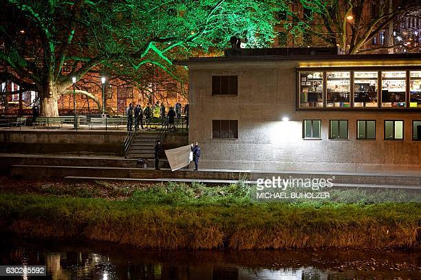 Swiss police officers hold a blanket to cover a dead body found near a Muslim prayer hall central Zurich on December 19 after three people were...