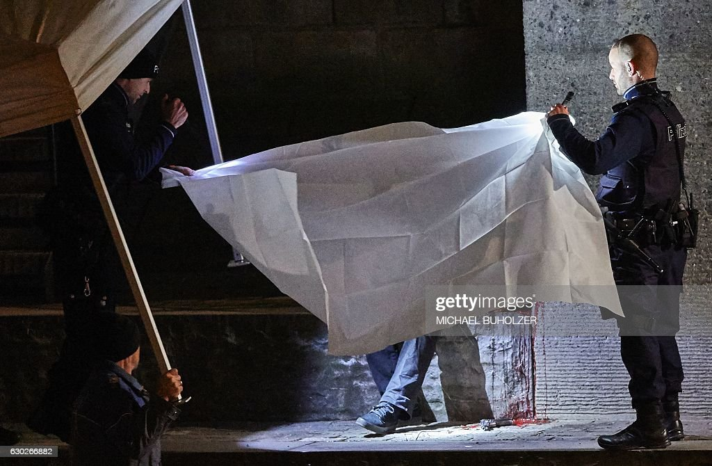 TOPSHOT - Swiss police officers hold a blanket to cover a