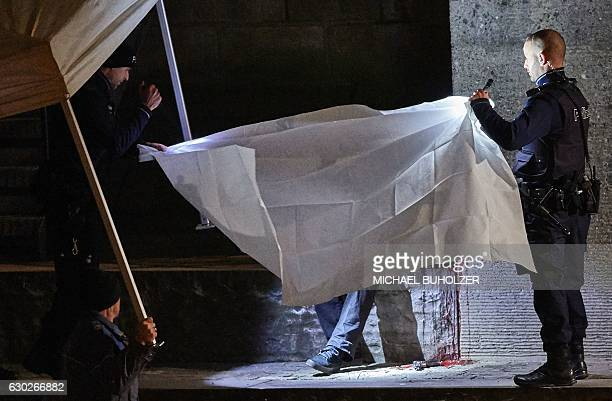 TOPSHOT Swiss police officers hold a blanket to cover a dead body found near a Muslim prayer hall central Zurich on December 19 after three people...