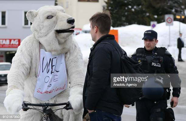945bc1a2b3f5 Swiss police officers take security measures as a demonstrator with a polar  bear costume protests US