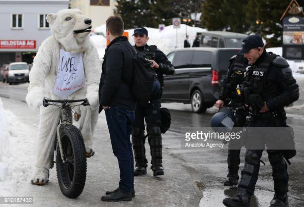 Swiss police officers take security measures as a demonstrator with a polar bear costume protests US President Donald J Trump during the 48th World...