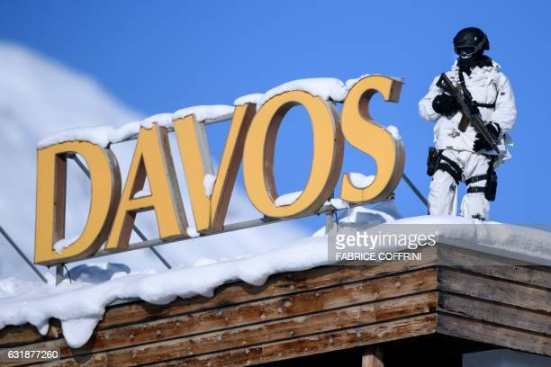 A Swiss police sniper stands guard on the roof next to the Congress centre during the first day of the World Economic Forum on January 17 2017 in...