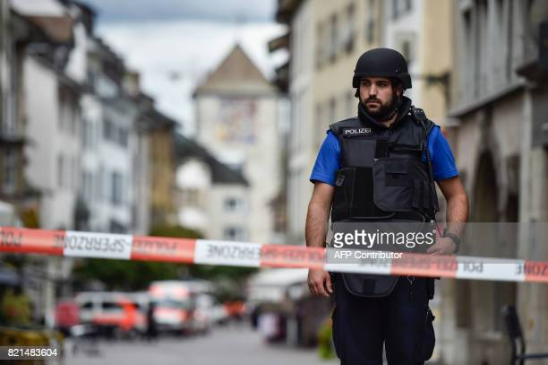 A Swiss policeman is seen standing guard behind a police cordon in the old quarter of Schaffhausen northern Switzerland on July 24 after a man armed...
