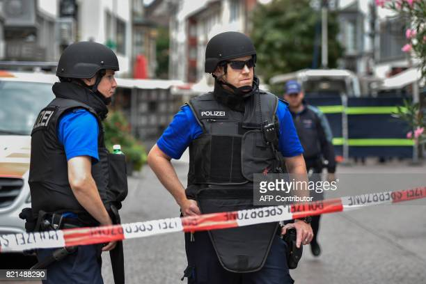 Swiss policemen stand guard behind a police cordon in the old quarter of Schaffhausen northern Switzerland on July 24 after a man armed with a...